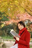 Young asian sensual woman reading a book in romantic autumn scenery.Portrait of pretty young girl in autumnal forest Stock Image