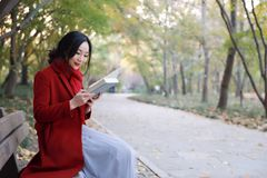 Young asian sensual woman reading a book in romantic autumn scenery.Portrait of pretty young girl in autumnal forest Royalty Free Stock Image