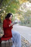 Young asian sensual woman reading a book in romantic autumn scenery.Portrait of pretty young girl in autumnal forest Stock Photography