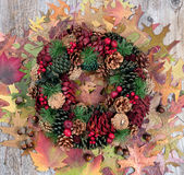 Autumn cone wreath and leaves on rustic wooden boards Royalty Free Stock Photos