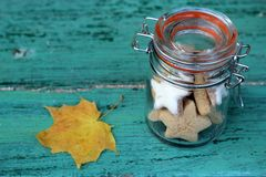 Autumn cookies in a retro glass jar. And leaf on a blue wooden background Royalty Free Stock Images
