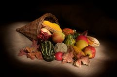 Autumn Cornucopia. Wicker cornucopia with seasonal autumn fruit and vegetables spilling out Stock Photography