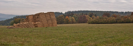 Autumn countryside with meadow, haystacks, forest and hills Royalty Free Stock Photography