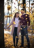 A coupe in love stands under the autumn falling leaves in the park. Autumn. A coupe in love stands under the autumn falling leaves in the park royalty free stock photos