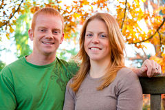 Autumn Couple. A man and a woman sit outside on a bench under fall colors of trees in a park Stock Photography