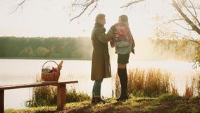 Autumn couple. Beautiful couple in warm clothes standing near the lake, where reflected the autumn sky, faded , picnic. Autumn couple. Beautiful couple in warm stock video footage
