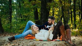 Autumn couple in love hug. Young lovers enjoying each other at a picnic. Woman lying down on the man`s leg and having a stock photos