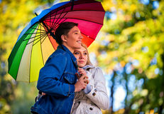 Autumn couple walking park. Fall friends walk under rain umbrella. Stock Photography