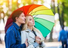 Autumn couple walking park. Fall friends walk under rain umbrella. First date of two young people in rainy day. First spring rain Royalty Free Stock Photography