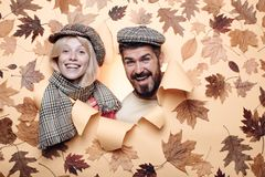 Autumn couple wearing in autumn clothes and looks very sensually. Bearded man in cap and blond girl with scarf are happy stock photo