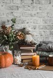 Autumn cozy home still life. Pumpkin, stack of books, burning candle, pile of winter autumn sweaters, jar of marshmallows, cup,