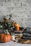 Autumn cozy home still life. Pumpkin, stack of books, burning candle, pile of winter autumn sweaters, jar of marshmallows on the