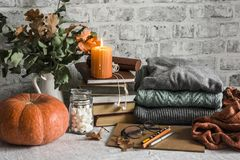 Autumn Cozy Home Still Life. Pumpkin, Stack Of Books, Burning Candle, Pile Of Winter Autumn Sweaters, Jar Of Marshmallows On The Royalty Free Stock Photos