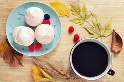 Autumn cozy mood - a cup of coffee, marshmallow, marmalade berries, autumn yellow leaves on a wooden background. Top view Stock Photos