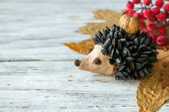 Autumn crafts. Children`s fall crafts and creativity, Hedgehog made from modeling clay, sunflower seeds and nuts, on dry yellow l royalty free stock photos
