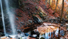 Autumn creations. Colorful waterfall in the forest during autumn season Stock Photography