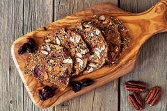 Autumn crisp bread with cranberries, nuts and seeds on paddleboard Stock Photo