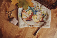 Autumn cross stitch design with mushrooms on wooden table Stock Image