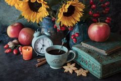 Autumn Cup of coffee and cookies. Beautiful flowers and cup of coffee with cookies , autumn decor with apples, old book, candle and alarm clock stock photos