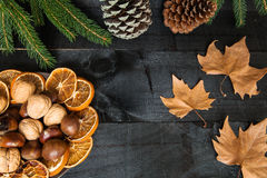 Autumn cutlery dinner decoration. Composition of cutlery on wood background for branches and a decorative dry oranges, pain fruit and leafs for informal dinners Royalty Free Stock Images