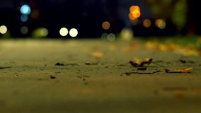 Park in autumn dark night. Alone man walks on the sidewalk. View from blurred background. Helios lens. stock image