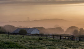 Autumn dawn, with an orange light through the early morning mist Royalty Free Stock Images