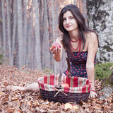 Autumn day. Young woman sit in red leaves with a basket with apple Stock Photography