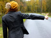 The autumn day the car broke down and the girl in a dress with a hat catches another car to help stock photo
