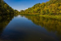 Autumn deciduous forest and river on a sunny day. Amazing landscape. Ukraine. Europe royalty free stock photography