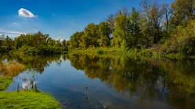 Autumn deciduous forest, water river and the river bank on a sunny day. Amazing landscape. Ukraine. Europe stock image