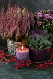 Autumn decor with candle and flowers Stock Photos