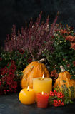 Autumn decor with candle and pumpkins. Autumn decor at home with a candles, pumpkins and autumn flowers Stock Photos