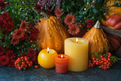Thanksgiven decor with pumpkin and candle. Autumn decor at home with a candles, pumpkins and autumn flowers Stock Photography