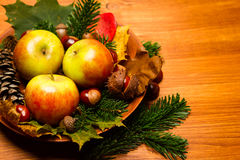 Autumn decoration. With apples, acorn, chestnut and a fircone in a wooden bowl on white wood Stock Photos