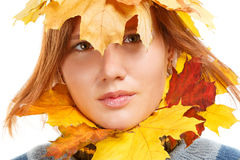 Autumn decoration. Beautiful young woman in striped sweater with decoration of autumn leaves isolated on white background royalty free stock photography