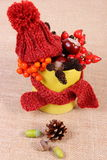 Autumn decoration with cup wrapped scarf and woolen cap on burlap Royalty Free Stock Image