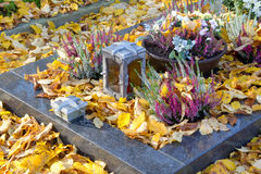 Autumn decoration on the tomb full of leaves. Stock Photo