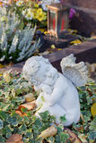 Autumn decoration on the tomb with white angel. Royalty Free Stock Photography