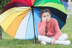 Autumn depression. Spring style. depressive mood in autumn rainy weather. Little girl tired under colorful umbrella. Multicolored umbrella for little happy stock photo
