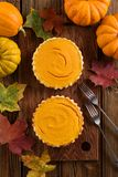 Autumn dessert flatlay. Couple of small simple pumpkin pies decorated with bright orange pumpkins and marple leaves. Overhead view stock photos