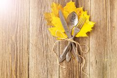 Autumn dinner place setting for Thanksgiving holiday with colorful maple leaves on rustic wooden boards. Toned stock images