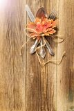 Autumn dinner place setting for Thanksgiving holiday with colorful maple leaves on rustic wooden boards. Toned stock image