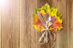 Autumn dinner place setting for Thanksgiving holiday with colorful maple leaves on rustic wooden boards. Toned royalty free stock photo