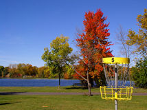 Autumn Disc Golf III. Hole 5, close up view of an innova disc cathcher, stands against a fall color display.  A lake reflects the pure blue sky in the background Stock Photography
