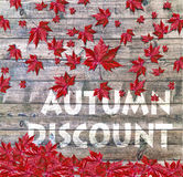 Autumn Discount and red falling leaves laying on wooden background Royalty Free Stock Image
