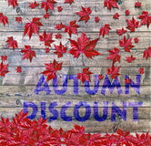 Autumn Discount and red falling leaves laying on wooden background Stock Photos