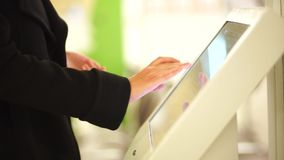In the autumn dressed woman using the self services terminal to pay on the fare. stock video footage