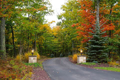 Autumn Driveway. A rural driveway entrance with pillar lights shown in autumn with colorful trees and shrubs Stock Photos