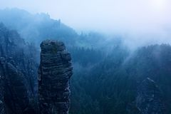 Autumn early morning view over sandstone rocks to fall valley of Saxony Switzerland. Sandstone empire and hills in mist. Stock Photos