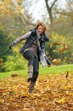 Autumn Enjoyment. European woman kicking yellow leaves in autumn. She has a happy expression on her face Royalty Free Stock Photography